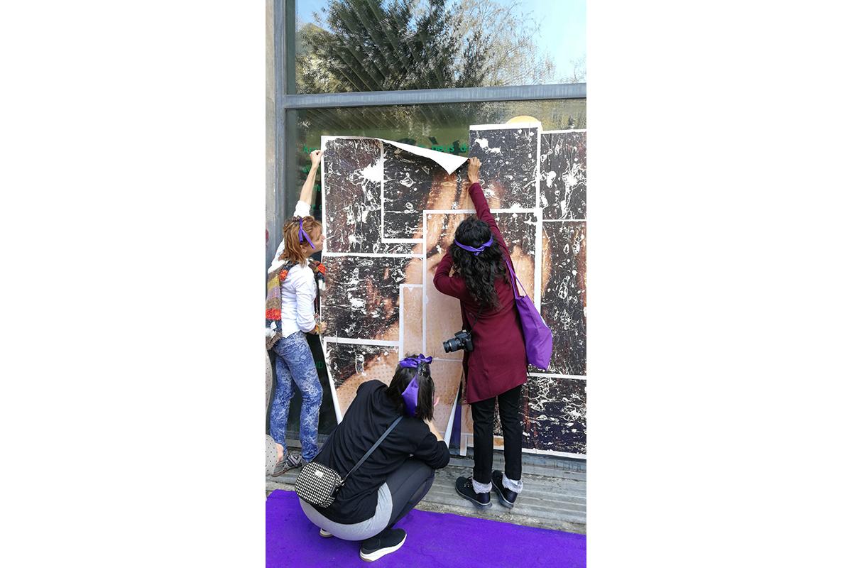 Dones penjant una de les imatges al Centre Cívic Pati Llimona.